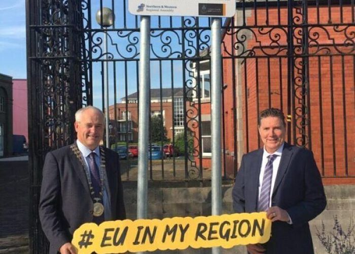 Two men holding eu in my region sign