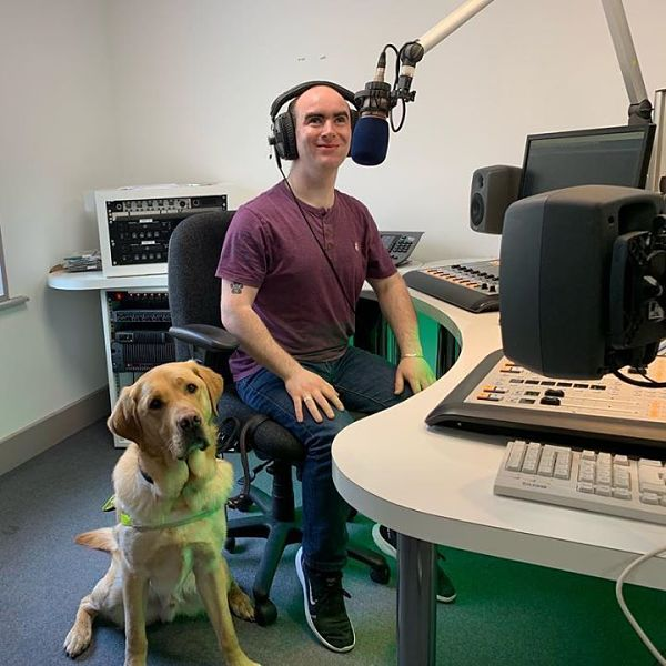 Participant Dara and his guide dog Hansen in the radio station studio